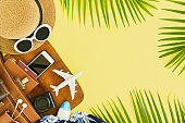 Top view of traveler accessories, tropical palm leaf and airplane on yellow banner background with copy space for text.Travel summer holiday vacation concept.