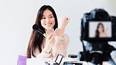 Asian beautiful woman blogger is showing how to make up and use cosmetic. In front of the camera to recording vlog video live streaming at home.Business online influencer on social media concept.