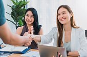 Beautiful young Asian girl and businesswoman meeting & shake hands at a office space with a laptop on table. Concept of female leader working business success.