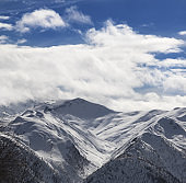 Snowy winter mountains and blue sky with sunlight clouds