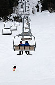 Two skiers on chair-lift in gray winter day