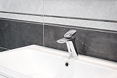 Luxury faucet mixer on a white sink in a beautiful gray bathroom
