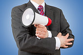 businessman holding a megaphone isolated on blue background