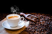Withe cup filled with hot coffee surrounded by roasted coffee beans