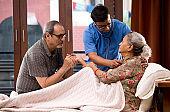 Home caregiver examining senior woman using stethoscope on bed
