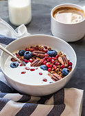 Homemade granola, muesli with pomegranate seeds, blueberries, pecan nuts and yogurt on gray concrete background