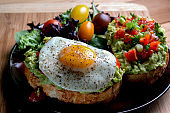 Avocado Toast Topped With Diced Tomatoes Chopped Green Onion Drizzled With Olive Oil And Fried Egg