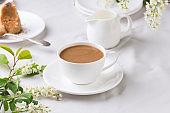 Creamy Coffee in white mug with bird-cherry tree blossom
