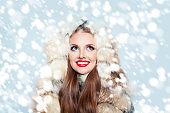 Pretty woman in fur coat on winter snow background