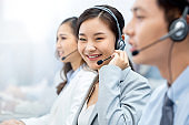 Smiling beautiful Asian woman working in call center office