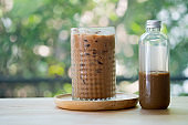 Iced coffee mocha in a tall glass and bottle on table