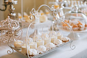 Wedding reception dessert table with delicious decorated white cupcakes