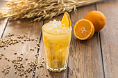 fresh squeeze natural orange juice in clear drinking glass and wheat spikes on wooden table