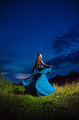 Beautiful blond model in blue air dress posing on the green meadow