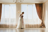Bride standing alone with bridal bouquet near a big window