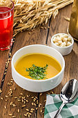 Pumpkin and carrot cream soup and wheat spikes on wooden table