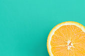 Top view of a one orange fruit slice on bright background in turquoise green color. A saturated citrus texture image
