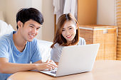 Asian young couple using laptop computer think and searching internet together, man and woman casual smiling work at home with happy and relax, communication and business concept.
