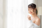 Portrait of beautiful young asian woman standing the window and smile while wake up with sunrise at morning, girl happy with freshness and cheerful, lifestyle and relax concept.