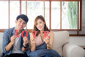 Beautiful portrait young asian couple sitting on sofa holding word love together in living room, family husband and wife smiling with happy, man and woman lover wearing casual with relax, lifestyle concept.