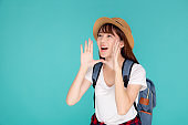 Beautiful young asian woman shouting sound loud with mouth for announce something in vacation travel with excited isolated on blue background, tourist asia girl journey in summer concept.