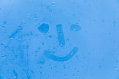 The picture or figure of the smiling face on the blue evening or morning window glass with drops