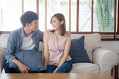 Beautiful portrait young asian couple relax and satisfied together in living room at home, family sitting couch confident with cheerful and happy with relationship, man and woman dating.