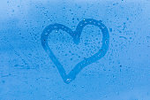 The child picture or figure of the heart on the blue evening or morning window glass with drops