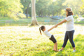 Young asian mother and little daughter playing the park with fun and happiness, family enjoy and relax and leisure together, mom and children smiling laughing in summer day.