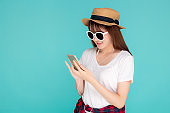 Beautiful portrait young asian woman listening music on phone with earphone isolated on blue background, asia girl using smartphone excited and fun with relax in travel summer trip concept.