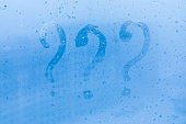 The three question marks picture or figure on the blue evening or morning window glass with drops
