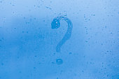 The question mark picture or figure on the blue evening or morning window glass with drops