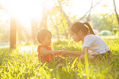 Beautiful young asian kid sitting playing in summer in the park with enjoy and cheerful on green grass, children activity with relax and happiness together on meadow, family and holiday concept.