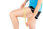 Closeup caucasian leg slim of woman with measure isolated on white background, girl wear sport with measuring centimeter tape for healthy and diet, cellulite and calories for health care.