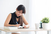 Beautiful young asian woman smiling sitting study and learning writing notebook and diary in the living room at home, girl homework, business woman working on table, education concept.