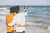Back view gay portrait young couple smiling taking a selfie photo together with smart mobile phone at beach, LGBT homosexual lover in the vacation at sea, two man going to travel, holiday concept.