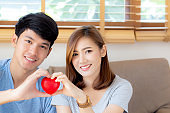 Beautiful portrait young asian couple gesture holding heart shape together, man and woman cheerful smiling and happy sitting on couch, family relationship with love, romantic and sweet concept.