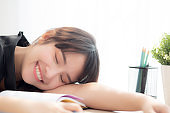Beautiful portrait young asian woman smile and happy writing learning exam or homework and lying with desk, lifestyle beauty asia girl with work, education and business concept.