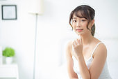 Portrait of beautiful young asian woman smile while wake up healthy and wellness with sunrise at morning in the bedroom, asia girl skin care with happy with fresh, lifestyle and relax concept.