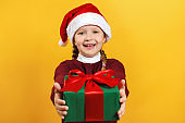 Happy child with christmas present. Little girl in santa claus hat gives a gift on a yellow background
