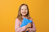 Portrait of a merry little blond girl on a yellow background. A child in a pink shirt and book is looking into the camera. The concept of education.