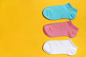 Closeup set of short socks in white, pink, blue on a yellow background with copy space