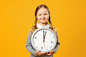 Closeup portrait little girl child holding big clock on yellow background. The concept of education, school, time management, development, timing, time to learn.