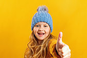 Cheerful little girl in a sweater and hat, showing thumb up, looking at camera on a yellow background.