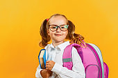 Portrait of little girl schoolgirl with backpack and book on yellow background. Charming child student closeup. Back to school. The concept of education.