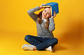 A cheerful little student girl is sitting on the floor with a book on her head. Education and school concept
