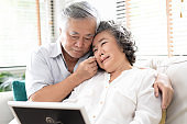 Sad frustrated mature old woman in tears feeling blue thinking of loneliness sorrow grief, husband comforting his upset wife together while sitting on sofa and looking at old photographs in picture frame at home