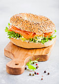 Fresh healthy bagel sandwich with salmon, ricotta and lettuce on vintage chopping board on white kitchen table background. Healthy diet food. Pepper on the side