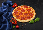 Fresh round baked Pepperoni italian pizza with tomatoes with basil on black background with blue linen towel.