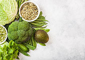 Assorted green toned raw organic vegetables on white background. Avocado, cabbage, broccoli, cauliflower and cucumber with trimmed beans and pumkin seeds in white bowl.